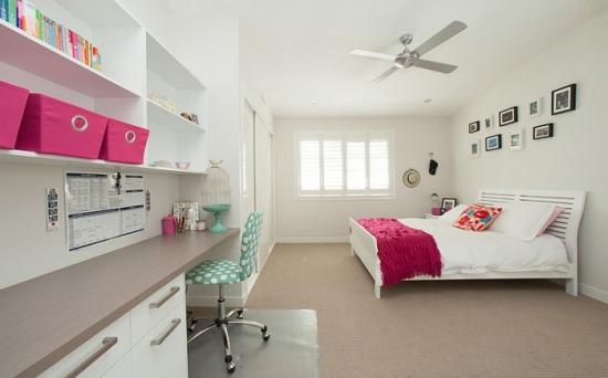 Dormitor alb cu accente roz si spatiu de lucru amenajat pe un perete