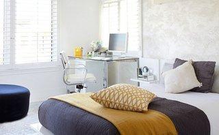 Dormitor alb cu pat pe mijloc si masuta pe post de birou