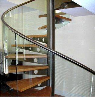 Scara interioara in spirala cu trepte din lemn si balustrada din inox si sticla