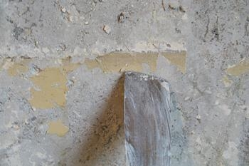 Curatarea cu spaclul a peretilor afectati de mucegai