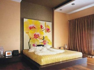 Dormitor modern cu tablou mare cu orhidee