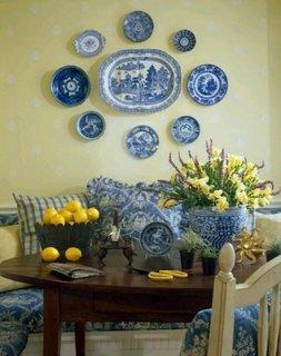 Colectie de farfuri din portelan alb cu albastru dispusa pe perete