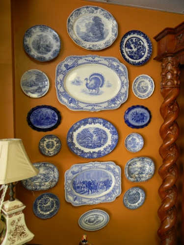 Colectie de farfurii alb cu albastru pe un perete portocaliu