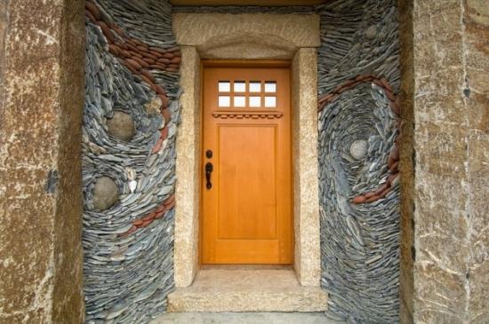 Perete fatada casa placat cu piatra de rau dimensiune medie si mica