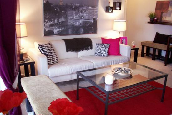 Camera de zi mica cu canapea alba din piele si perne decorative colorate
