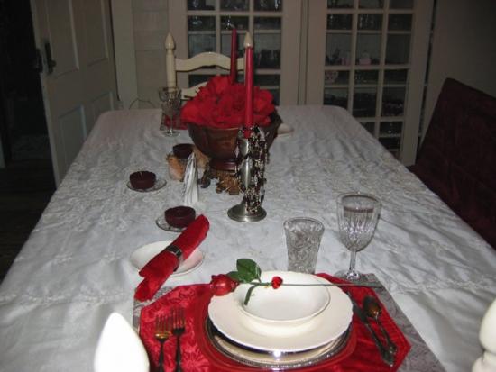 Masa cu fata de masa si farfurii albe si accesorii rosii romantice