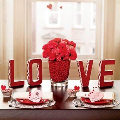 Mesaj de dragoste din litere rosii din lemn si vaza cu flori