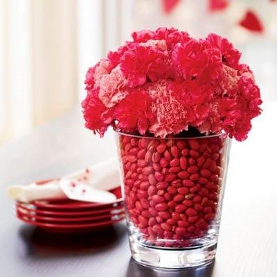 Vaza din sticla transparenta cu garoafe rosii si roz