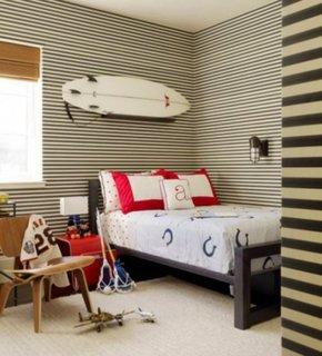 Dormitor modern pentru copii cu o placa de surf deasupra patului