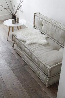 Canapea mica in nuante neutre accesorizata cu un material din blana