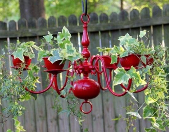 Candelabru reciclat cu flori agatat in gradina