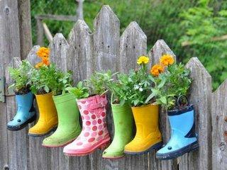 Cizmulite colorate cu flori in ele atarnate de gard