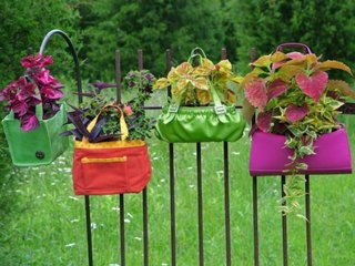 Posete reciclate cu flori agatate de gard in gradina