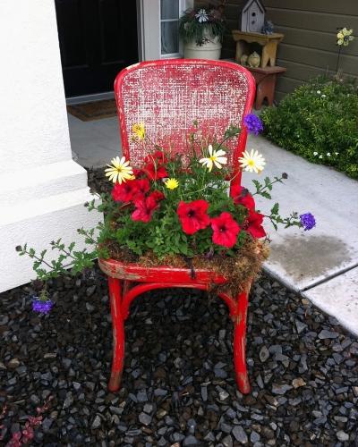 Scaun vechi reciclat pentru depozitarea florilor in curte
