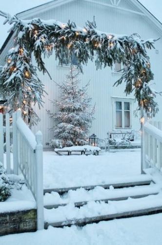 Exterior al casei decorat cu felinare in zapada