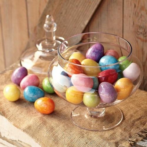 Bol de sticla cu oua colorate asezat pe panza de sac