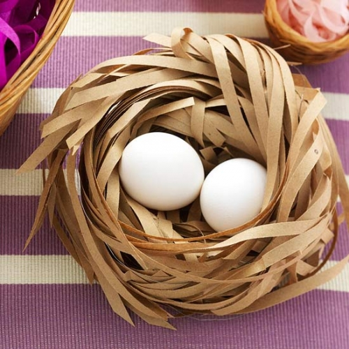 Cuib realizat din fasii de hartie cu doua oua albe in el