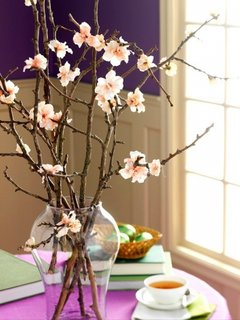 Vaza inalta asezata pe masa cu ramuri de copac inflorite