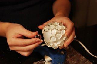Instalatie pentru brad de Craciun cu becuri mari albe simple pe care au fost lipite pietricele