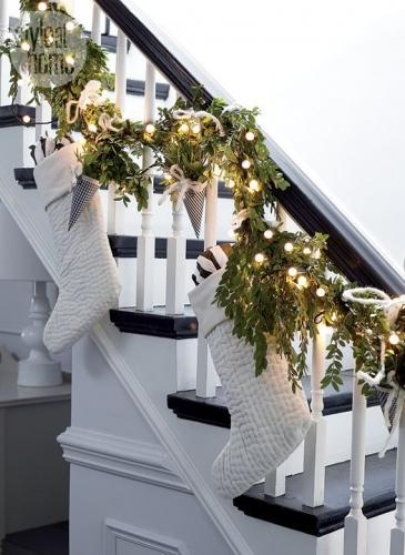Decoratiuni de Craciun asortate cu o scara de interior alba cu trepte si balustrada din lemn