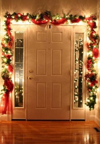 Usa de la intrare decorata cu ghirlande funde si lumini