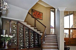 Dulap cu rafturi pentru sticle de vin perete de accent in spatiul de sub scara