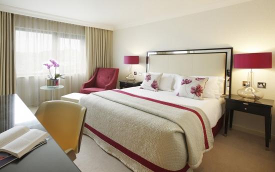 Dormitor amenajat romantic cu pat matrimonial pe mijloc si fotoliu in colt