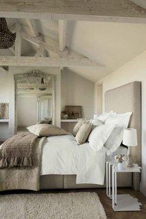 Oglinda mare prinsa in perete intr-un dormitor rustic