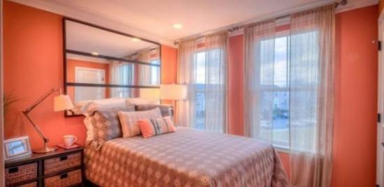 Dormitor amenajat in culoarea piersicii si oglinda mare deasupra patului