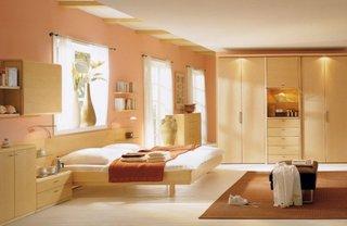 Mobila de dormitor din lemn natur si pereti zugraviti culoarea piersicii