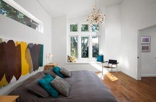 Dormitor alb mare cu pat amplasat langa perete si pictura abstracta in culori tari