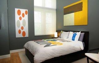 Dormitor modern cu tablouri mari dispuse pe pereti si pereti gri carbon