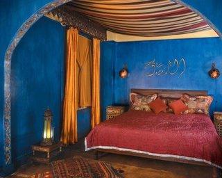 Dormitor marocan cu peretii albastru safir si accesorii rosii rubiniu