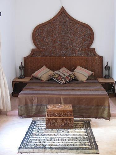 Pat amplasat pe mijloc cu tablie de pat inalta din lemn cu motive traforate