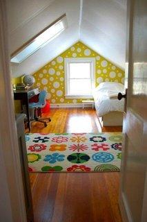 Dormitor la mansarda cu perete de accent galben cu buline albe