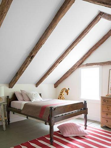 Dormitor simplu amenajat la mansarda cu covor tesut rosu cu alb