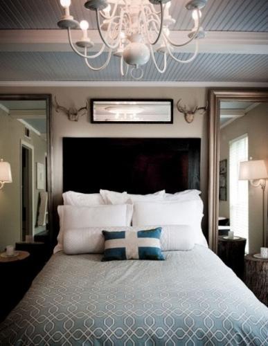 Dormitor simplu cu pat pe mijloc si multe perne decorative