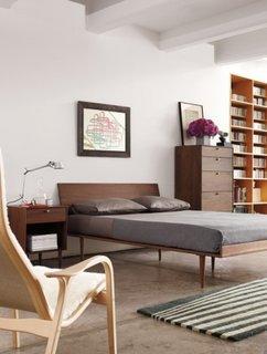 Dormitor simplu si practic cu pat si comoda inalta si biblioteca incorporata in perete