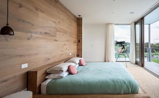 Perete de accent placat cu lemn in spatele patului