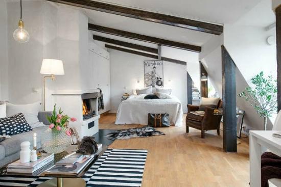Dormitor cu grinzi din lemn masiv si covor in dungi