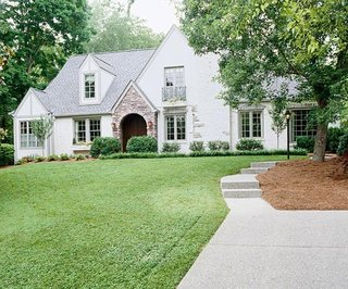 Casa cu acoperis gri si fatada alba cu combinatie de caramida