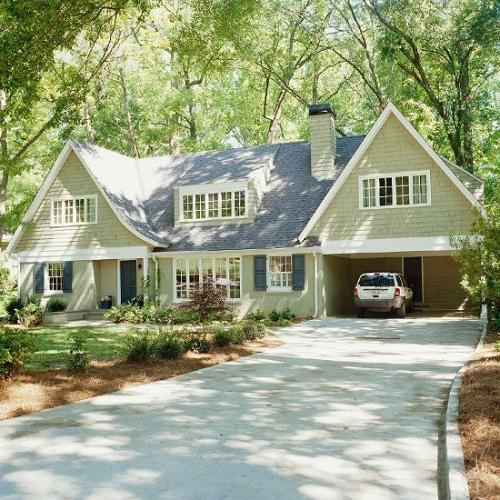 Casa cu un etaj cu garaj la parter cu fatada crem cu alb si acoperis gri petrol