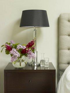 Vaza cu flori si veioza decorativa asezate pe noptiera