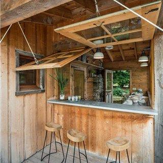 Cabana de lemn rustica cu ferestre de lemn cu deschidere verticala pentru terasa