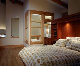 Dormitor matrimonial cu baie tip loft cu pat pe mijloc