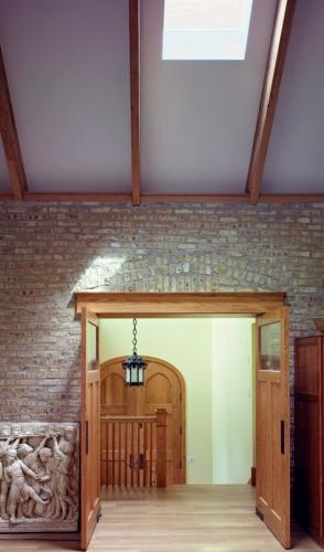 Hol de la etaj cu caramida pe perete si usa dubla din lemn masiv