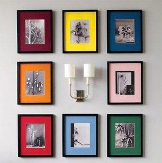 Aranjament cu tablouri cu poze in jurul aplicei de perete