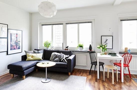 Canapea gri cu otoman asezata langa fereastra din living mic