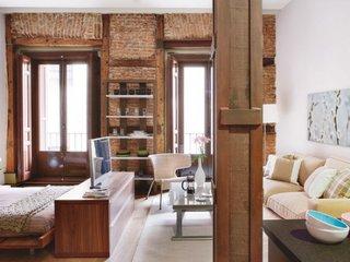 Aparatament tip studio amenajat cu mobila din lemn masiv si perete cu caramida