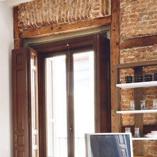Perete in apartament tip studio placat cu caramida aparent veche